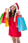 Festive brunette holding shopping bags — Stock Photo