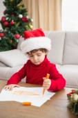 Festive little boy writing wish list — Stock Photo