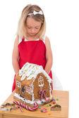 Festive little girl making gingerbread house — Stock Photo