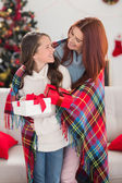 Festive mother and daughter wrapped in blanket with gifts — Stock fotografie