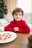 Festive little boy having milk and cookies — Stock Photo