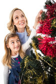 Festive mother and daughter decorating christmas tree — Photo