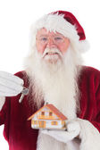 Santa hands the key to a tiny house — Stock Photo