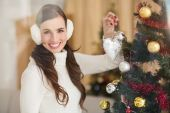 Smiling brunette holding heart near a christmas tree — Stockfoto