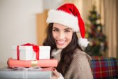 Festive brunette holding pile of gifts at christmas  — Stock Photo