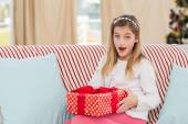 Cute little girl sitting on couch with gift — Foto de Stock
