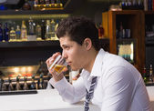 Young man drinking whiskey neat — Stock Photo