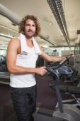 Man standing by exercise bike at gym — Stockfoto