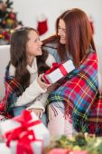 Festive mother and daughter wrapped in blanket with gifts — Stock Photo