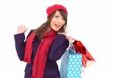 Happy brunette in winter clothes holding shopping bags — Stock Photo