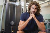 Handsome trainer sitting in gym — Stock fotografie