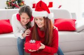 Festive mother and daughter with a christmas gift — ストック写真