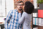 Young woman kissing man in office — Stock Photo