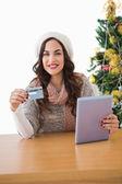 Festive brunette shopping online with tablet pc — Stock fotografie