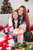 Festive mother and daughter wrapped in blanket with gifts — ストック写真