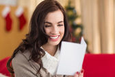 Smiling brunette on the couch reading letter at christmas  — Stock Photo