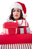 Confused brunette holding pile of gifts — Stock Photo
