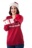 Happy brunette in santa hat offering gift — Stock Photo