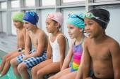 Cute swimming class smiling poolside — Stock Photo