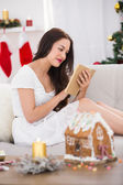 Relaxed brown hair reading on the couch at christmas  — Stock Photo