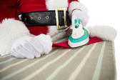 Father christmas ironing his hat  — Stock Photo
