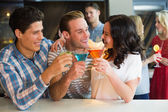 Young friends having a drink together — Stock Photo