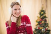 Portrait of a pretty smiling blonde wearing earmuffs — Stock Photo