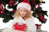 Festive little girl holding a gift — Stock Photo