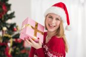 Smiling festive woman showing a pink gift — ストック写真