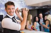 Handsome barman smiling at camera making a cocktail — Stock Photo