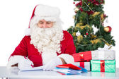 Happy santa writing letter for gifts — Stockfoto
