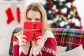 Young woman hiding behind a gift — Stock Photo