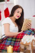 Uvolněné bruneta čtení na gauči s krytem — Stock fotografie