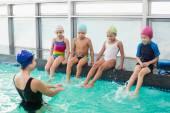Cute swimming class watching the coach — Stock Photo