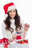 Smiling brunette in santa hat packing gifts — Stockfoto