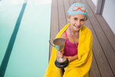 Cute little girl sitting poolside wrapped in towel — Stockfoto