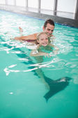 Girl learning to swim with coach — Stock Photo