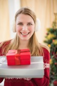 Smiling blonde wearing earmuffs while holding gifts — Stock Photo