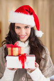 Festive brunette in santa hat holding gifts — Stock Photo