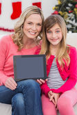Festive mother and daughter showing tablet screen — Stock Photo