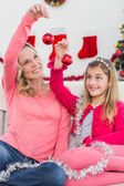 Festive mother and daughter smiling at camera — Stock Photo