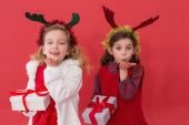 Festive little girls holding gifts — Stock Photo
