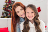 Festive mother and daughter on the couch — Stock Photo