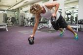 Man exercising with kettle bells in gym — Stock Photo