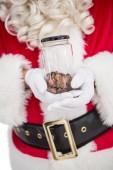 Santa holding jar full of pennies — Stock Photo