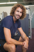 Handsome trainer sitting in gym — Stock fotografie