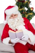Relaxed santa reading on the couch — Photo