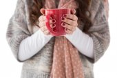 Woman in winter clothes holding a hot drink — Stock Photo