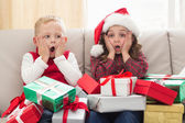 Festive siblings surrounded by gifts — Stock Photo