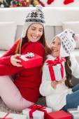 Mother and daughter exchanging gifts at christmas — Stock Photo